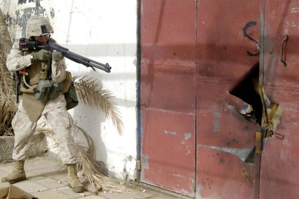 Американский солдат выбивает дверь